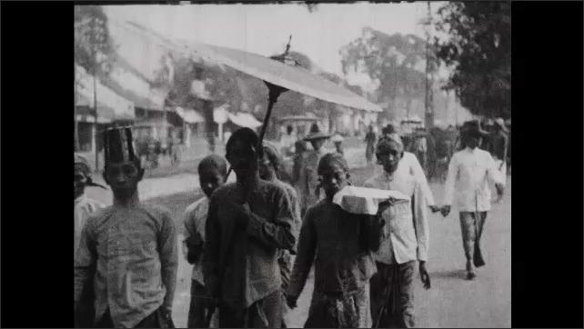 1930s: People walk down city street.
