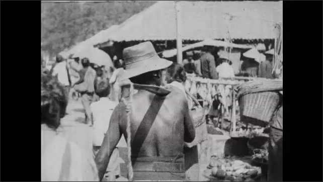 1930s: People walk around outdoor market.