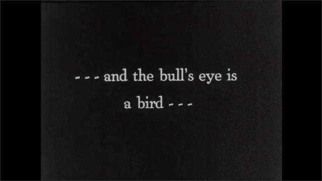 1930s: Men sit on ground, shoot arrows. Intertitle card. Arrows shoot into bird sculpture.