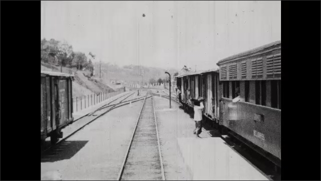 1930s: Train travels along track. Train pulls into station, people wait at station.