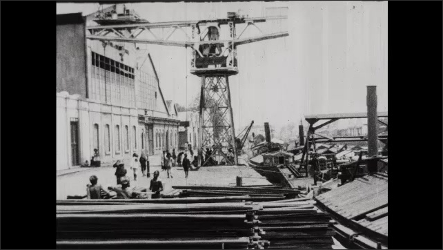 1930s: People on dock. Crane on dock. Boats at dock.
