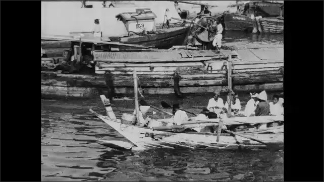 1930s: Men load boxes onto ship. Ships travel along water.