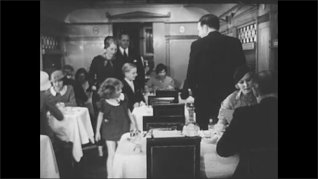1940s: Interior of train car, family sits at table.