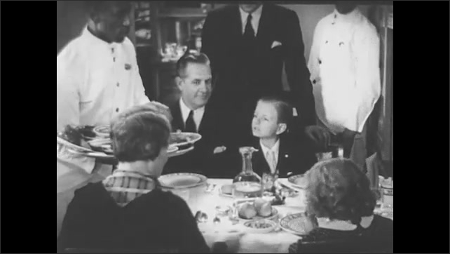 1940s: Family eating in train dining car, waiter puts food on table.