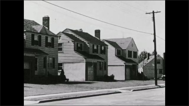 1930s: UNITED STATES: houses in empty street. Wooden panel houses. Electricity pole in street