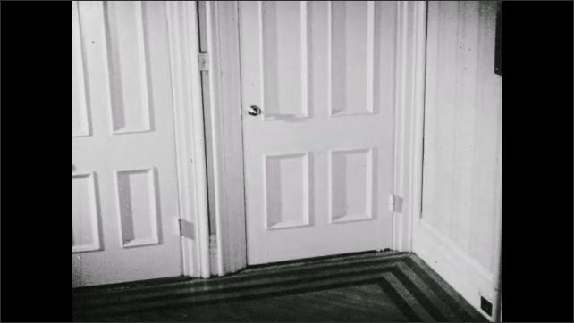 1930s: UNITED STATES: girl opens door in house. Girl closes door. Girl walks through door.