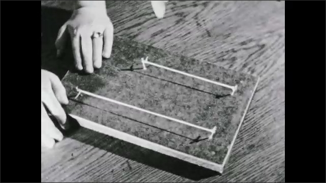 1930s: UNITED STATES: finger plucks rubber band on board. Pitch experiment with rubber bands.