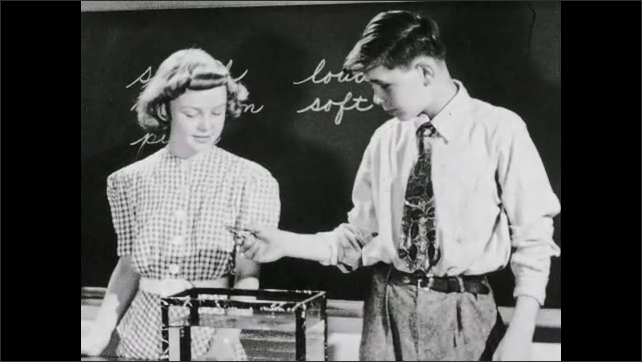 1930s: UNITED STATES: yard stick creates sound. Boy puts toy frog in water. Girl scratches wood.