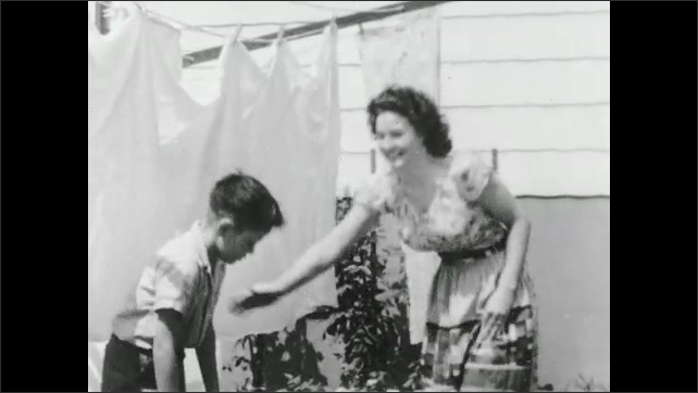1930s: UNITED STATES: lady hangs out washing on line. Lady wrings out fabric. Lady and boy carry basket from garden.