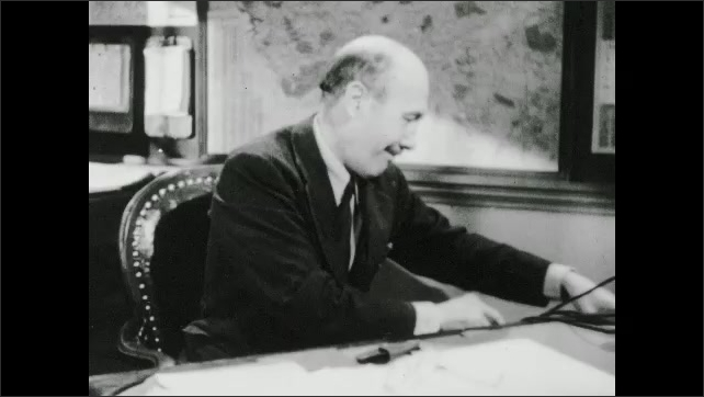 1930s: UNITED STATES: mother and son look at first on window. View across landscape towards mountain. Man picks up book in office. Man at desk. Boy looks at picture book and drawings.
