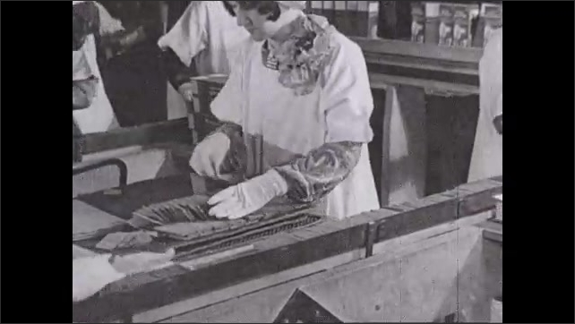 1930s: Women stack crackers and place them on to conveyor belts. Workers push stacks of crackers into boxes.