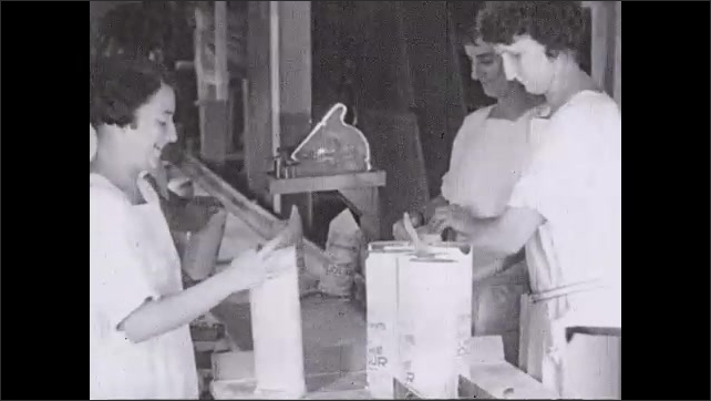 1930s: Open flour bags come off of conveyor belt. Women workers fold and seal whole what flour bags closed.