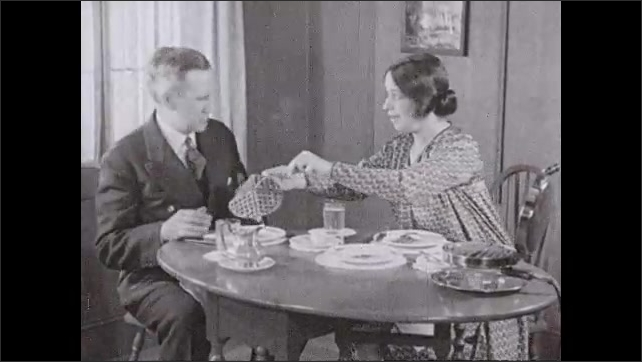 1930s: Waffle maker with waffle on it. Woman and man eat at the breakfast table. Woman takes waffle from waffle maker and places waffle on man's plate. Man pours syrup on waffle.