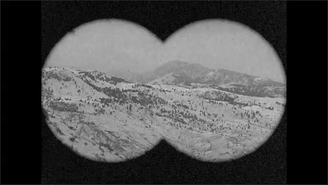 1930s: UNITED STATES: men stand on top of hill. View of mountains through binoculars. Hunters look for elk.