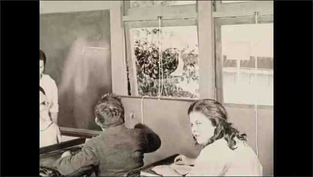 1930s: A boy reading at his desk in a classroom grabs his neck as if something hit him. He grabs a chalk eraser and throws it across the room, breaking a window. Another boy laughs.