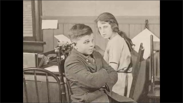 1930s: A boy stands in a classroom, in front of a man at a desk and other students. The man gestures and he leaves. Another boy looks nervous, and stands when he is called.