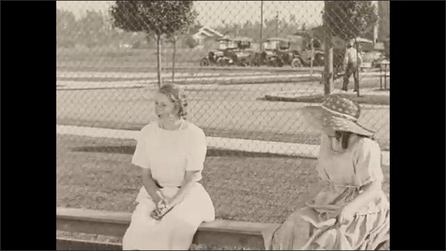 1930s: Kids play tennis on a court, then sit on a bench. A boy gets up and sits with another boy, who is sitting by himself.