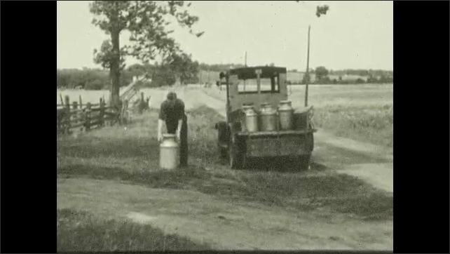 1930s: View of milk jug and buckets. Truck stops on road, man picks up milk jug, puts jug on truck.