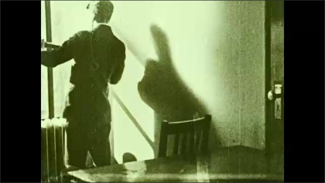 1930s: UNITED STATES: man looks at planets with telescope. Man looks through window with telescope. Planet moves in space