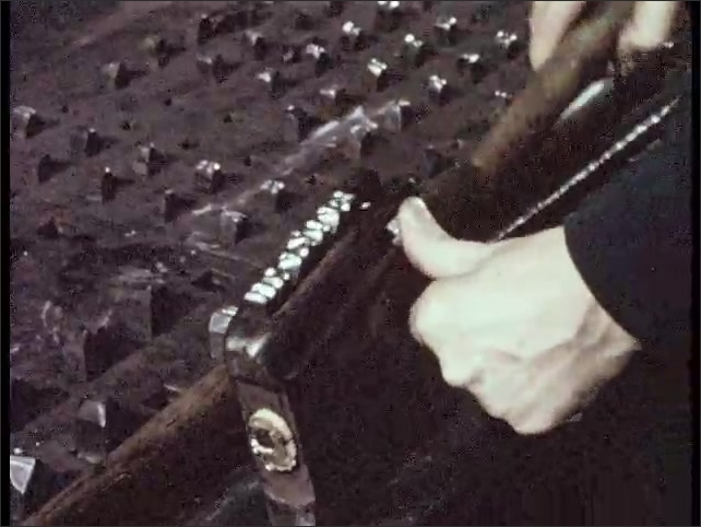 1950s: machine places ore inside furnace. hands hold complaint form paperwork. steel plate with cracks. hands pick up sledgehammer and stamps bar to number surface. metal rods on work horses.