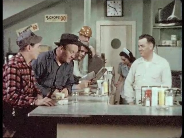 1950s: man in hat sits on stool at lunch counter, gets cook to fill his cup of coffee, talks and gestures to man in baseball cap at restaurant.