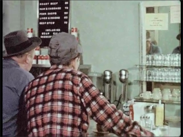 1950s: two men in suits put paperwork in folder at office. man in hat swivels on stool at lunch counter and shakes head with man in baseball cap as cook serves plates in restaurant.