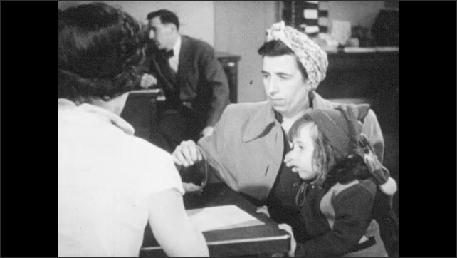 1940s: Woman sits behind a desk, talks to people, hands people papers, people sign papers.