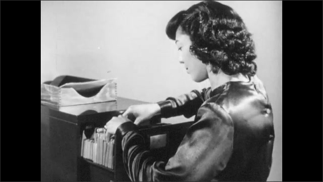 1940s: Woman types on typewriter, woman operates switchboard, man talks on phone, man types on stenotype, woman takes papers out of filing cabinet, man puts folder into briefcase, closes briefcase.