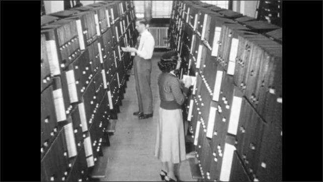 1940s: Woman looks at record books, writes on small paper. People walk through records room. Records pages.