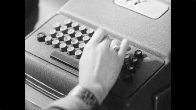 1940s: Woman holds punch card. Women type on machines. Cards runs through punch card machine. Man operates machine.