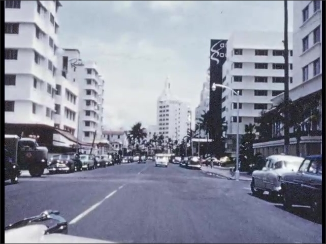 1950s: Island in the ocean. Car drives down city street. Tourists watch dolphins at waterpark.