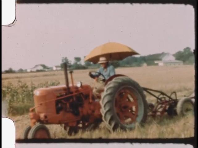 1940s: Tractor drags harrow across crop fields on farm. Farmer drives tractor across field.