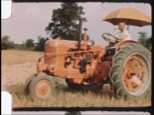 1940s: Man with pipe drives tractor over farm fields.