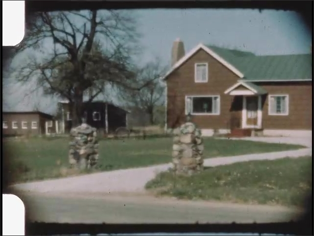 1940s: Home and open garage in rural yard. Driveway leads to open garage of home. Shed and coops near home in rural landscape.