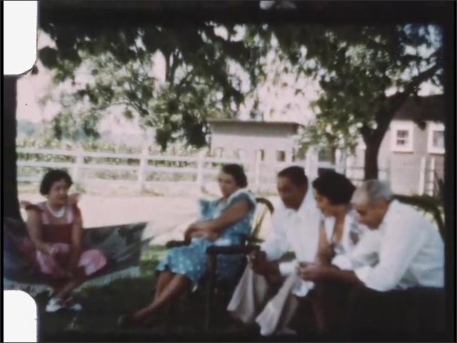 1940s: Family sits on chairs and hammock under tree. Men and women sit in yard and talk.