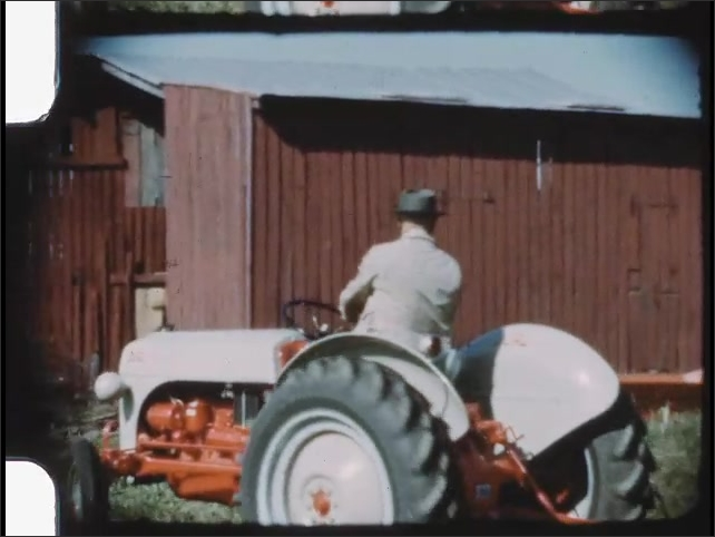 1940s: Man drives tractor near farming equipment and barn. Women stand near barn and watch tractor.
