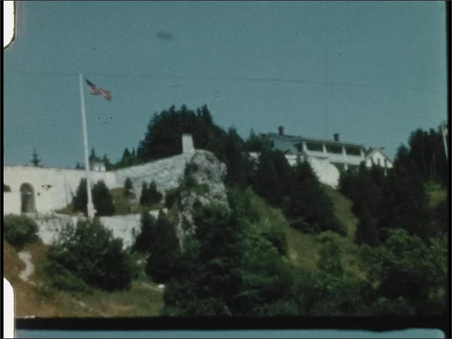 1940s: UNITED STATES: horses pull carriage along track. Fort Mackinac sign. American flag by stone wall.