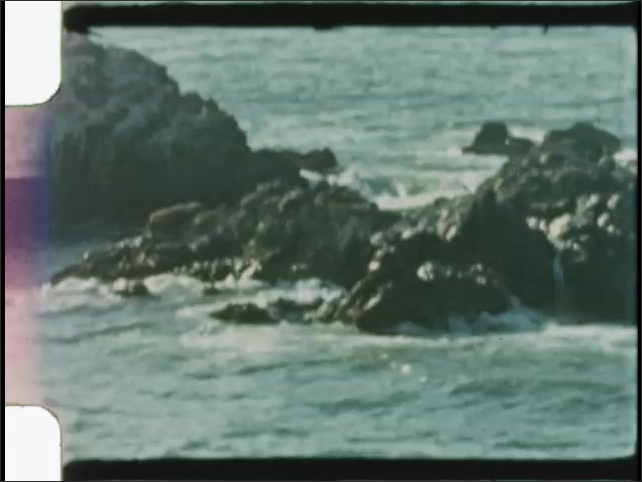 1940s: UNITED STATES: headstones and plants in cemetery. Rocks in sea. Waves on rocks.