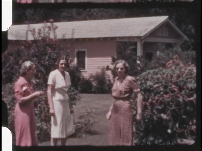 1930s: Two women stand on lawn talking and are joined by third woman. Three women stand together on lawn, holding strings.