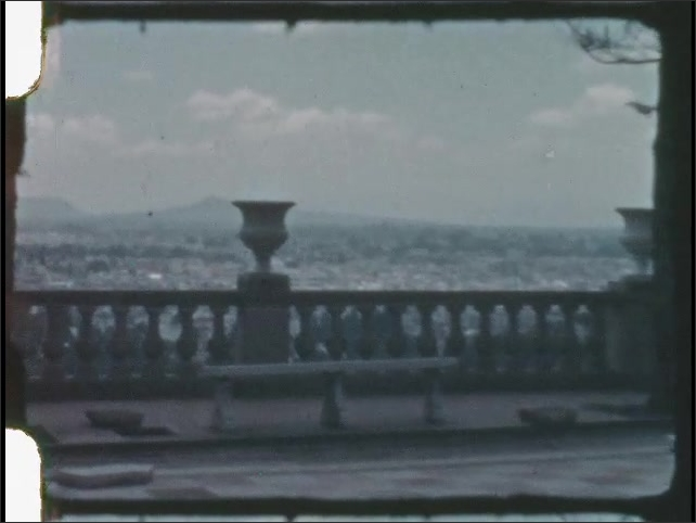 1930s: Looking out over city from terrace on building. Building on hill.