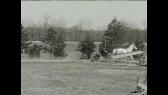 1940s: Horse pulls carriage around circular track, man holds reins, riding crop. Man follows on horseback. Fields, trees.