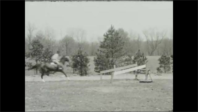 1940s: Man on horseback, woman pets horse's nose. People on horseback mill around parking lot, cars, building. Man on horseback jumps fence obstacles.