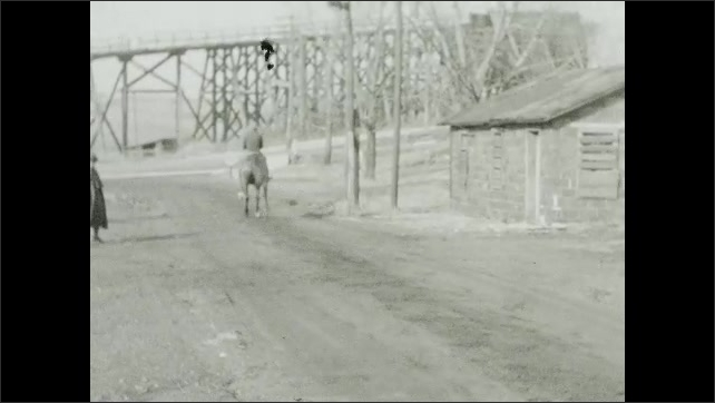 1940s: Trees, fields, man rides horse down dirt road towards paved road, traffic, cars, stops, turns around.