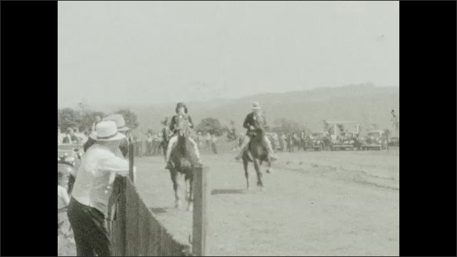 1940s: Parked cars, crowd leans over fence, watches people on horseback run quickly around circular track, race. Photographer kneels, takes item from pocket, stands, walks away.