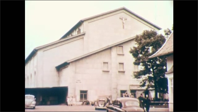 1960s: People are walking into large church. Car pulls up and drives by church.