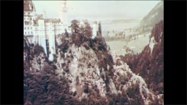1960s: Man and woman at table play harp and lyre as people sit at other tables around them. Castle-like building sits on top of mountain.