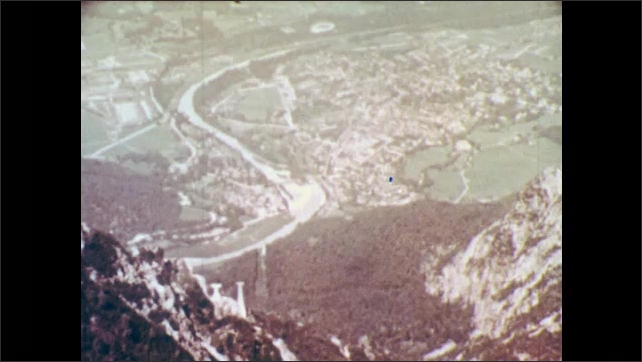 1960s: Large chandeliers hand in elaborate room inside mansion. Mountains. Town lies at base of mountains, in valley.