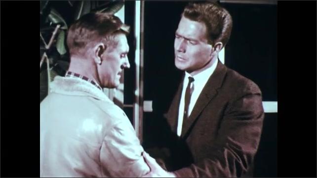1960s: UNITED STATES: man enters door. Men shake hands by door. Men talk.