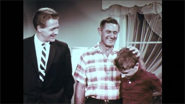 1960s: UNITED STATES: man talks to boy. Men talk in lounge