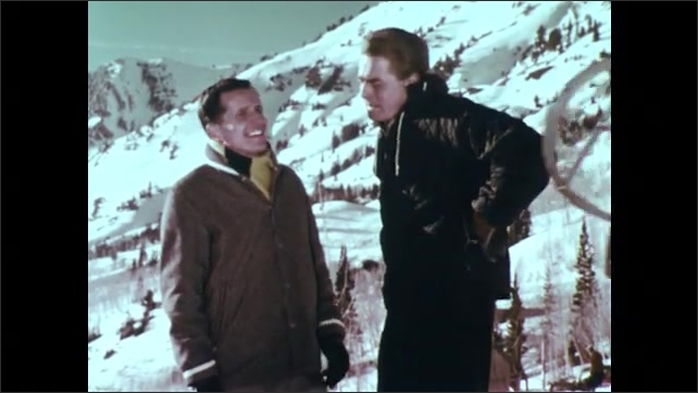 1960s: Snowy mountain.  Men talk.  Man pushes girl down hill on sled.